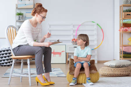 Young boy sitting on a yellow pouf with crossed arms listening to his psychotherapist during session Stock Photo