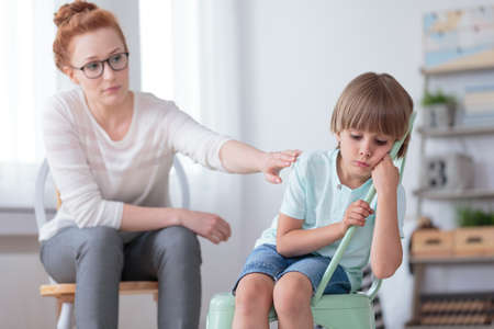Sad autistic boy sitting on a mint chair during session with red haired psychotherapist Stockfoto