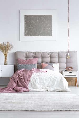 灰色のキングサイズのベッド、ベッドサイド キャビネットの銅の電話上のシルバーメタリック塗装で明るい寝室のカーペット 写真素材