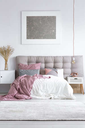 Grey carpet in bright bedroom with silver painting above king-size bed and copper phone on bedside cabinet Stock Photo