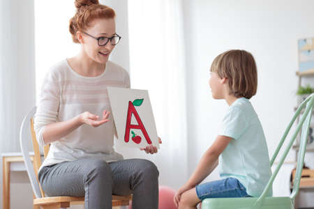 Young boy sitting on mint chair focusing on speech lessons with friendly speech therapist Stock Photo