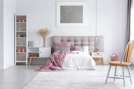 king size bed: Orange chair on grey carpet in bright bedroom with silver painting above king-size bed and copper phone on nightstand