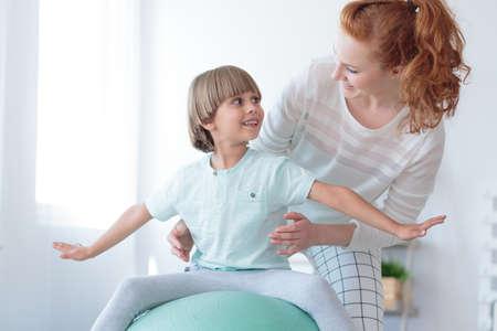 ミント ボール補正運動をして側弯症の少年を支える赤髪理学療法士 写真素材