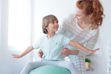 Rodeharige fysiotherapeut die jongen met scoliose ondersteunt die correctieoefening uitvoert op mintbal