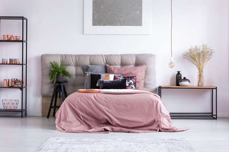 king fern: Copper phone and accessories on shelf in homely bedroom with pink overlay on king-size bed