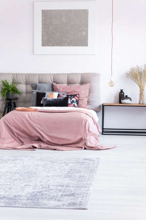 king fern: Grey carpet in minimal bedroom with silver painting above king-size bed with pink overlay