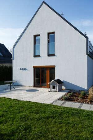 木製テラスのドアと緑の芝生と近代的なホーム外観