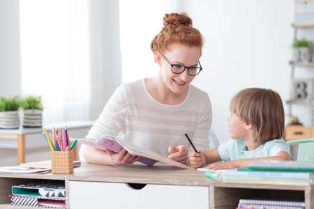 Glimlachende moeder die haar zoon helpt met huiswerk in het kantoor