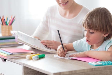 Boy focusing on his homework while sitting with mother at desk with notebook and colored pens