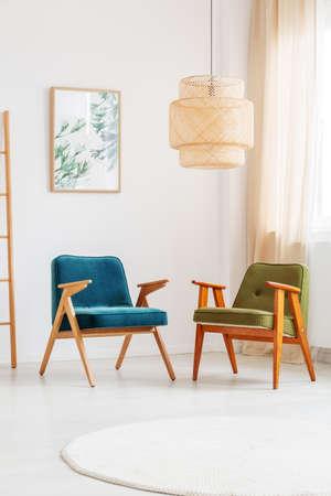 Lámpara hecha a mano sobre dos sillas vintage en habitación luminosa con pinturas con motivos florales en pared blanca Foto de archivo