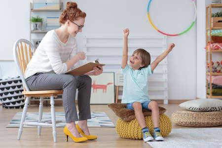 Chłopiec czuje się szczęśliwy, ponieważ osiągnął postępy w lekcjach mowy podczas spotkania z terapeutką mowy