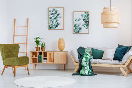 Pear green chair near cupboard with creative lamp in living room with white carpet and beige sofa