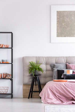 Plant in pot on black stool in stylish bedroom with copper accessories and pastel bedding on king-size bed
