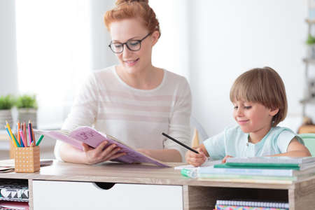 Math teacher doing exercises from workbook with young happy boy while sitting at desk in classroom Stock Photo