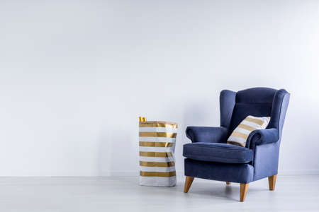 Stock Photo   Striped Gold Pillow On Dark Blue Armchair And Pattern Paper  Bag In Minimal White Room