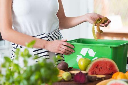 Mulher, reciclagem de resíduos de cozinha orgânica, compostagem em recipiente verde durante a preparação da refeição