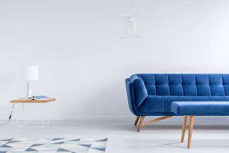 White lamp on table near geometric carpet in living room with navy blue couch and stool Stock Photo