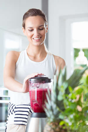 Healthy woman standing in kitchen and mixing beet smoothie in blender for fresh breakfast