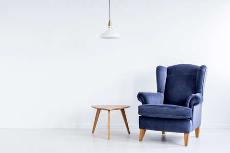 White lamp above wooden table next to dark blue classic armchair in spacious white room Foto de archivo