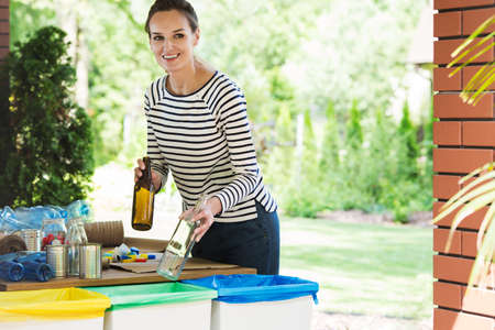 Segregating waste to correct containers, a daily routine of smiling young woman Editorial