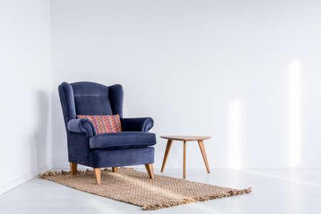 白いオープン スペースで小さなテーブルの横にある茶色のカーペットの上暗い青い肘掛け椅子の上にカラフルな枕 写真素材