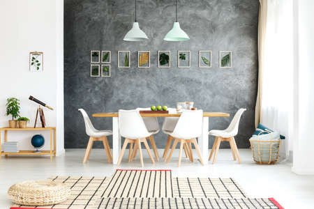 Artificial decorative leaves in wooden frames hanging on a textured wall
