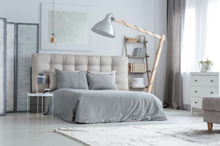 Modern grey bedroom with designed floor lamp next to bed Stock Photo