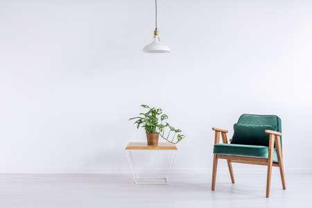 구리 양동이와 빈 거실에서 베개와 녹색 빈티지 안락의 자에 테이블 위에 흰색 램프