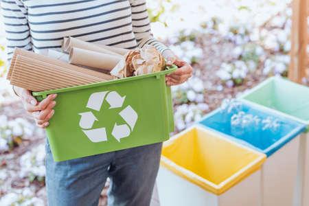 Ativista cuidando do meio ambiente, classificando os resíduos de papel na lixeira apropriada no terraço Foto de archivo