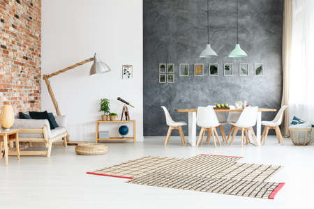 Bright asymmetric carpet with stripes on the floor in room with varied walls Stock Photo