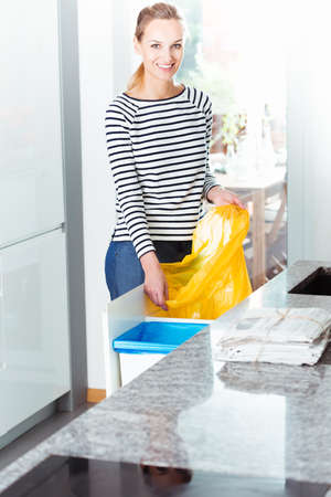Smiling woman cleaning modern kitchen and changing bin bag for recycling waste Imagens