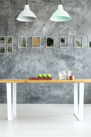 Grey textured wall with leaves in dining room with table and pastel lampshades Stock Photo