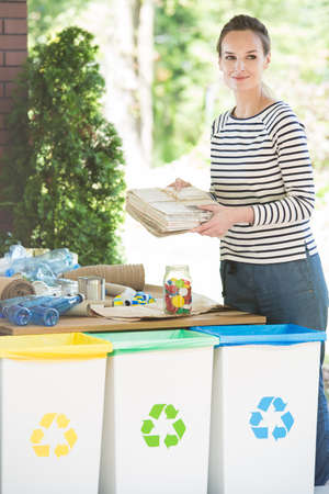 Young woman sorting waste everyday, putting paper waste to correct bin. Recycling concept