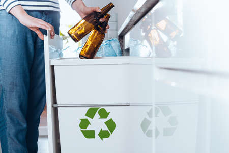 kitchen cabinets: Aware person sorting waste in modern kitchen with special bin with green symbol for glass bottles Stock Photo