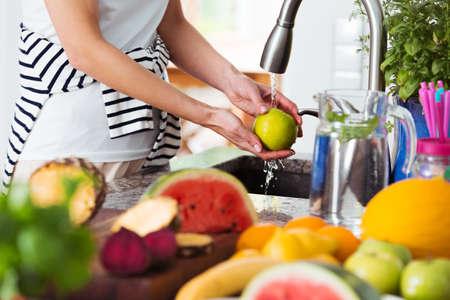 과일과 신선한 아침 식사를 준비하는 동안 부엌 싱크대 위에 사과 세척하는 건강한 여자