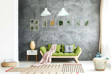 Pink coverlet falling off a green wooden sofa standing in the room with asymmetric carpet