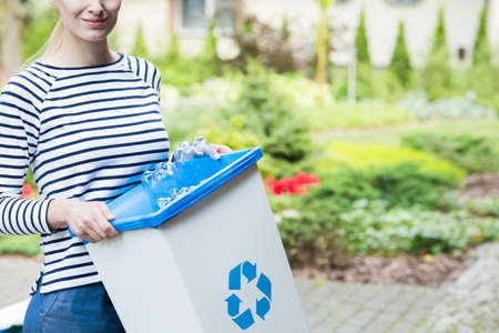 Smiling woman separating plastic bottles intended for recycling to bin with blue symbol