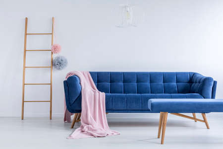 Colorful pompoms on ladder next to navy blue sofa with pink blanket in living room with stool Stock Photo