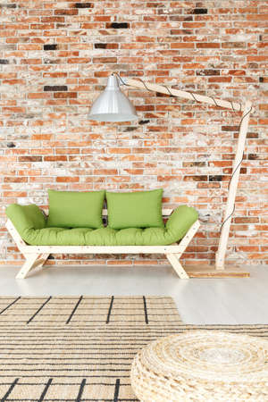 Oversize lamp standing next to green wooden lounge in room with brick wall Stock Photo