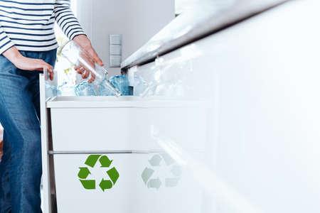 부엌에서 재활용을위한 유리 병을 분류하는 것은 모든 사람의 좋은 매일 습관입니다.