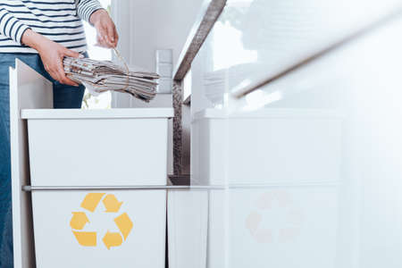 Responsible person sorting waste in modern kitchen with special bin with yellow symbol for paper