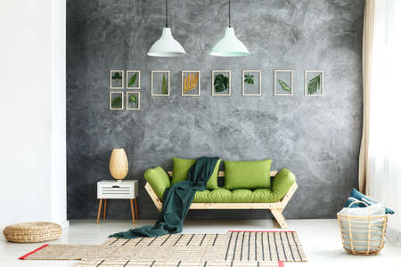 living room window: Dark green blanket thrown on wooden couch standing in living room with wicker basket and footrest Stock Photo