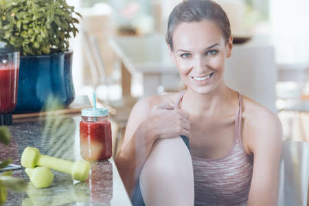 Smiling fit woman sitting on chair next to kitchen countertop with fruit cocktail and green dumbbells