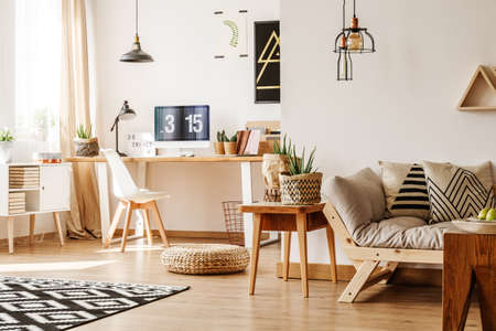 living room window: Modern loft interior full of natural wooden furniture and accessories with desk, computer, white chest, beige sofa, table and paper pots for plants
