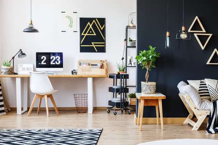 Nordic natural interior in stylish open studio for a freelancer with sofa, black wall and office space with desk and black accent