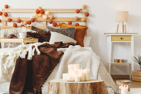 Many white candles standing on a tree trunk in bedroom Foto de archivo