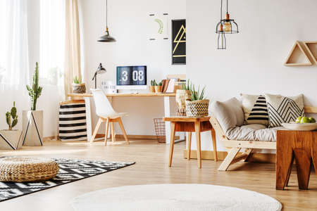 living room window: Interior design idea for home workspace with white wall, wooden furniture, simple desk with computer and designer chair in bright living area
