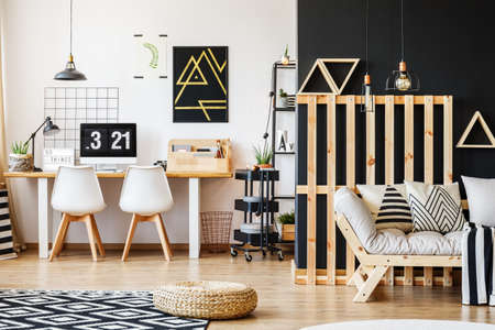 Big scandi desk, designer chairs, computer, poster and rack in modern cozy room for a teenager with black and white interior design and wooden pallet decor in living area with sofa