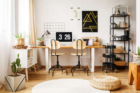 Nordic interior decor in modern room for teenager with poster, black rack, plants, pouf and storage cart on wheels standing next to wooden desk with computer in scandi style