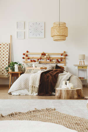 Big hand-made bed with warm blankets thrown on it Imagens - 85280782